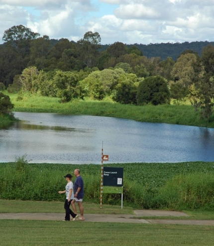 Couple walking along foot and cycle path in Minnippi Parklands next to lagoon.