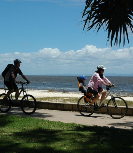 Family cycling on cycle path on Bribie Island with Moreton Bay ocean in background.