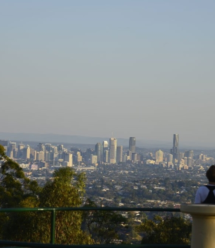 People standing on Mt Gravatt Lookout with views on to Brisbane city buildings.