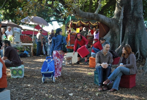 People sitting under a tree in the Davies Park Market with stalls in the background.